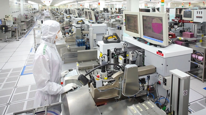 Uma equipe de produção da Micron vestindo touca, jaleco e máscara especiais para ajudar a manter uma sala limpa sem partículas