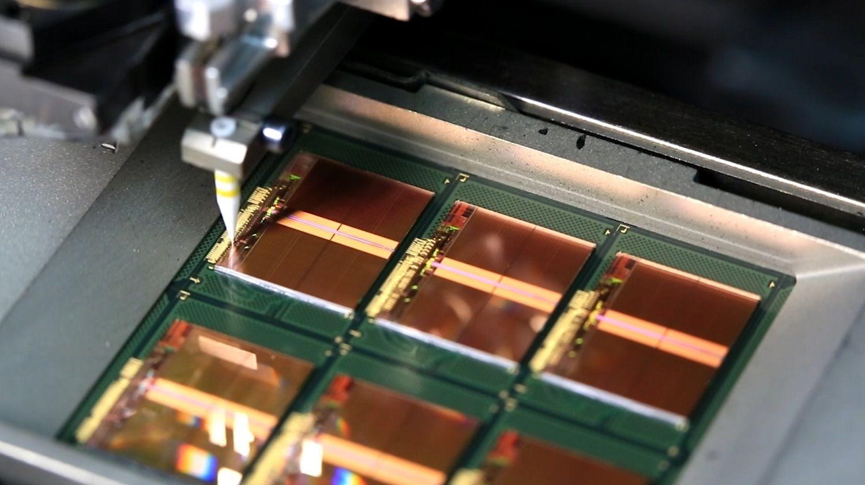 Fios finos de ouro conectando-se aos blocos de ligação do chip à estrutura como parte do processo de produção da memória