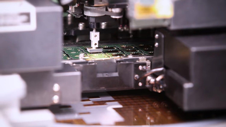 Uma máquina coletando um chip da esteira e aplicando-o à PCB