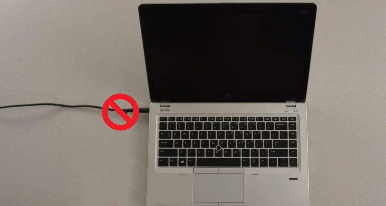 Um círculo cortado em cima do cabo de alimentação de um notebook para indicar que o cabo de alimentação deve ser removido antes da instalação