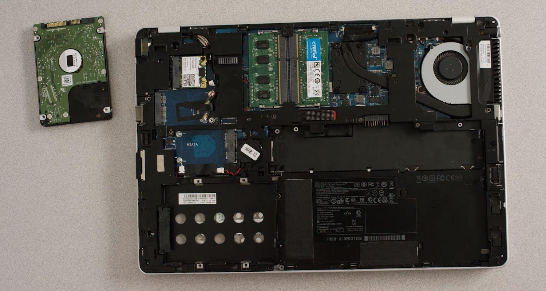 Disco de armazenamento antigo sendo removido do compartimento de armazenamento de um notebook