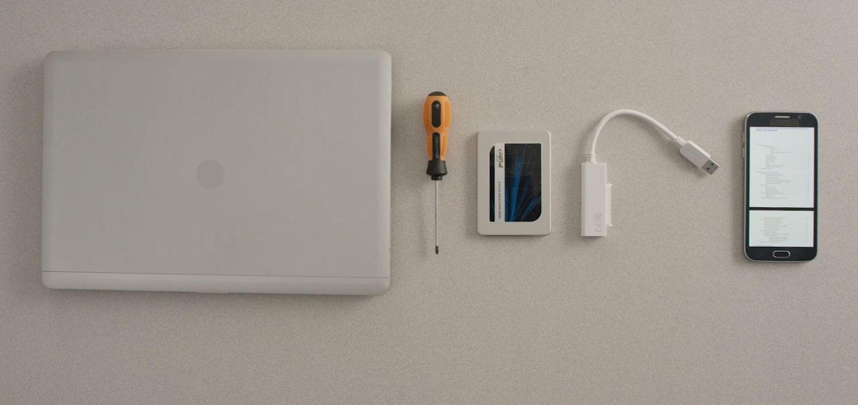 Um notebook, um SSD Crucial, uma chave de fenda e o manual do computador no celular dispostos sobre a superfície de uma mesa