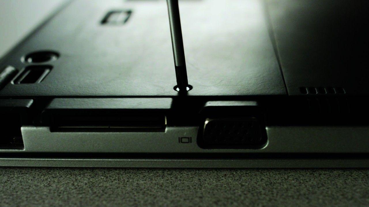 Chave de fenda removendo parafuso da parte traseira do notebook