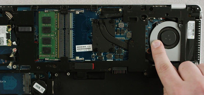 Dedo de uma pessoa tocando a superfície metálica sem pintura na parte inferior exposta de um laptop para descarregar a eletricidade estática.